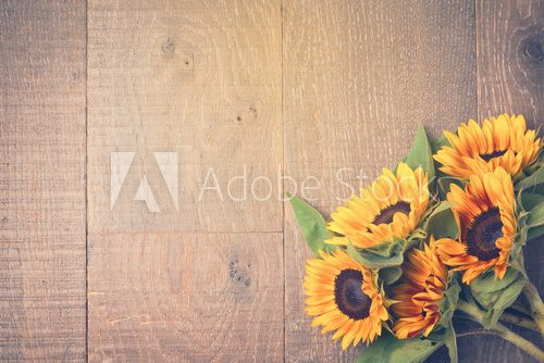 Fototapeta Autumn background with sunflowers on wooden table. View from above. Retro filter effect