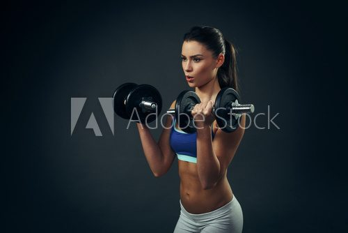 Fototapeta Beautiful young woman exercise with dumbbells on dark background