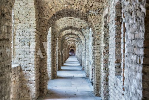 Fototapeta Castle tunnel with a series of arches in the ruined Bastion fortress in the Slovak city of Komarno.