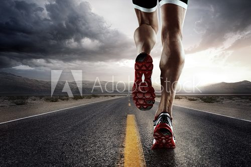 Fototapeta Sports background. Runner feet running on road closeup on shoe.