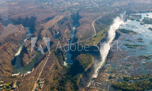 Fototapeta The Victoria falls is the largest curtain of water in the world. The falls and the surrounding area is the Mosi-oa-Tunya National Parks and World Heritage Site (helicopter view) - Zambia, Zimbabwe