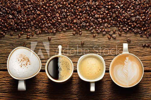 Fototapeta Variety of cups of coffee and coffee beans on old wooden table
