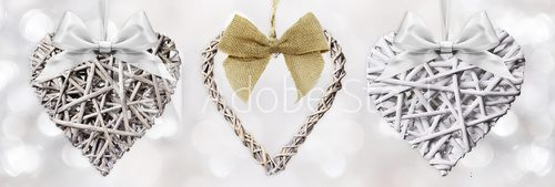 Fototapeta Wooden Hearts braided with ribbon bow isolated on silver blurred