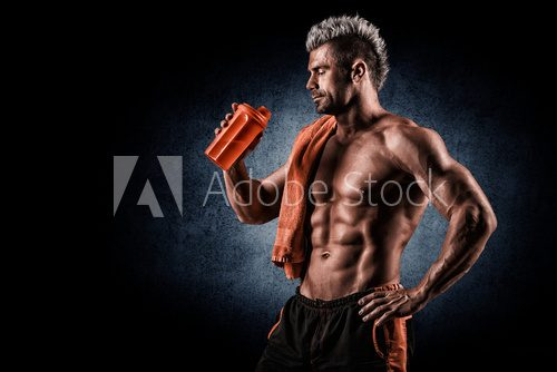 Fototapeta Young adult man drinking protein shake in gym. Black background.