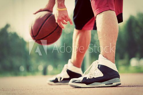 Fototapeta Young man on basketball court dribbling with bal